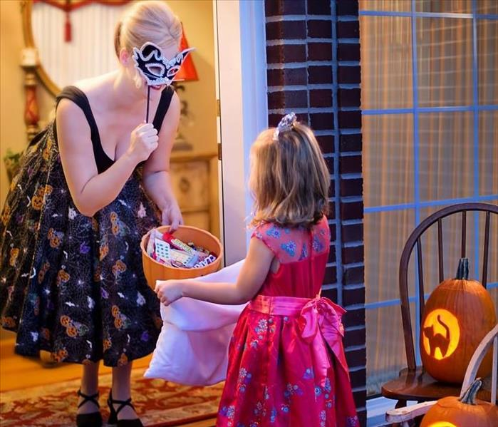 Setting is a front porch. A woman wearing a mask holding a basket of candy for a little girl in a red costume.