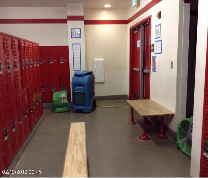 Locker room with red lockers to the left and red doors to the right. Dehumidifiers are located on the floor.