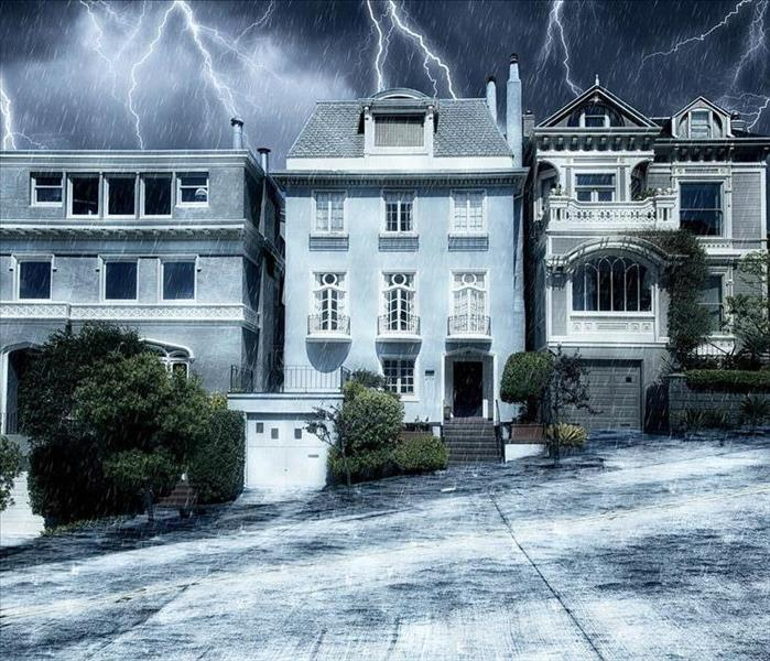 Three Victorian style homes in the center of a slanted uphill road with rain and lightning in the sky above them.