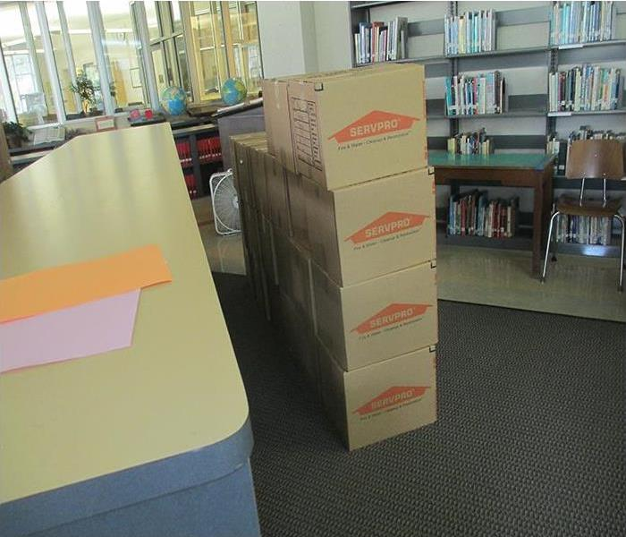 Cardboard boxes with the SERVPRO logo in the center of the room are stacked in 4 rows in a library.